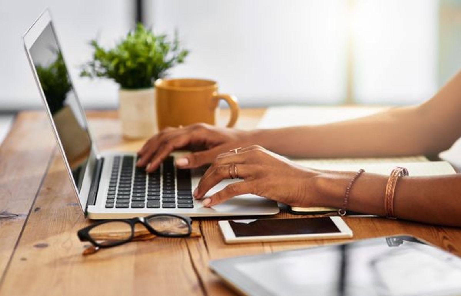 mains de femme qui navigue en ligne sur un ordinateur portable