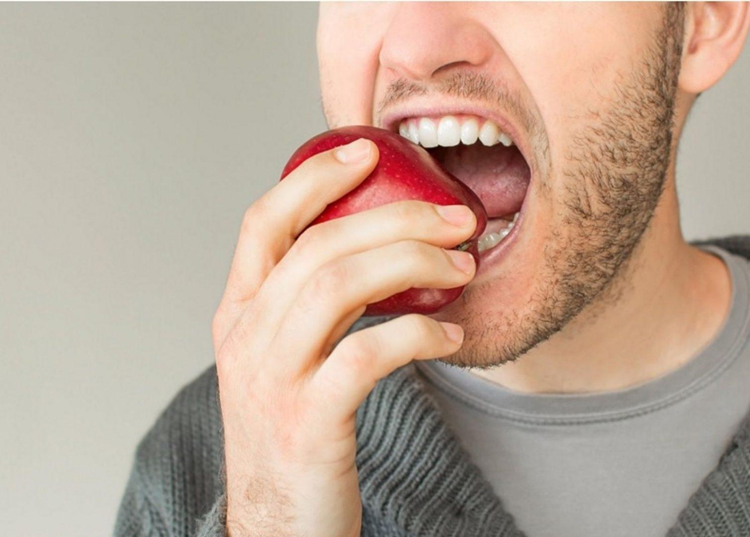 homme qui croque dans une pomme