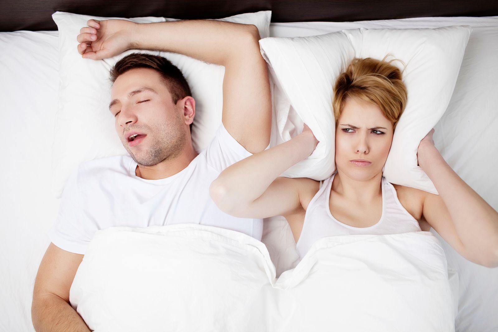 couple couché homme qui souffre d'apnée du sommeil