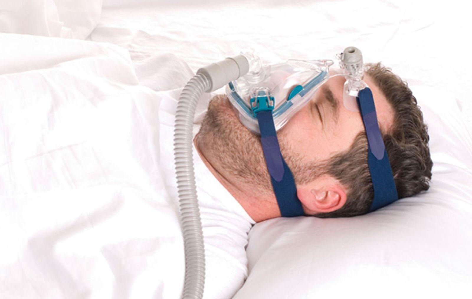 homme portant un appareil à pression positive continue pour l'apnée du sommeil